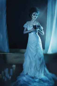 beautiful girl ghost, witch bride in a white dress holding a bla